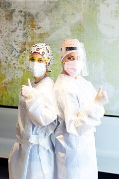 Doctor and assistant in protective workwear showing thumbs up while standing at office
