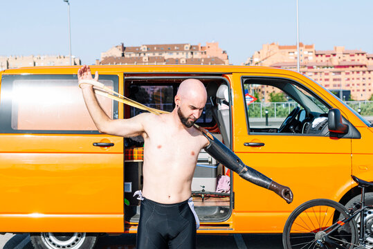 Bald adaptive athlete wearing artificial hand while standing against van
