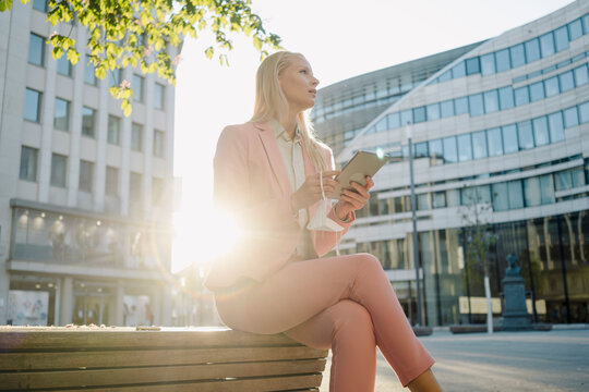 Back lit businesswoman holding digital tablet while sitting on bench and looking away in city