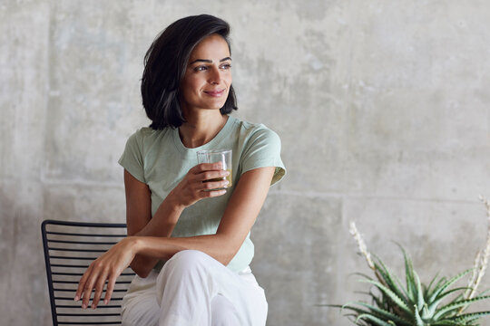 Smiling businesswoman holding smoothie while sitting on chair against wall in office