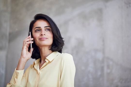 Close-up of businesswoman talking over smart phone against wall in office