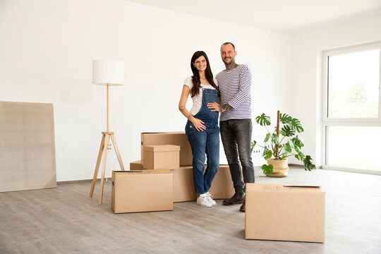 Happy couple standing by cardboard boxes and electric lamp in new unfurnished home