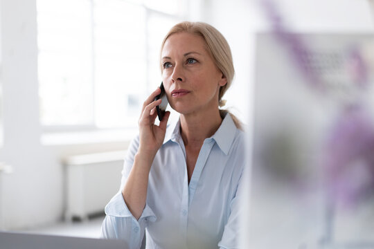 Confident businesswoman talking over mobile phone while sitting in home office