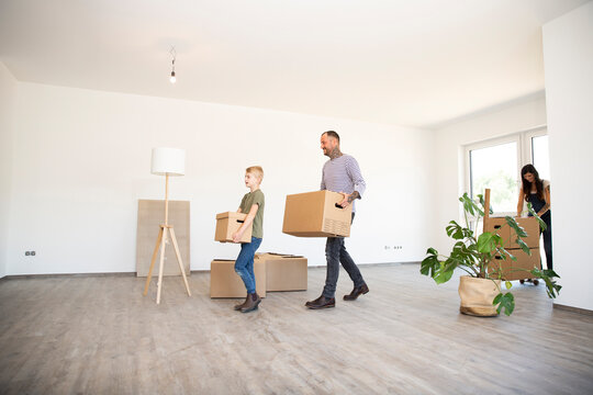 Father and son carrying cardboard boxes while walking on hardwood floor in new house