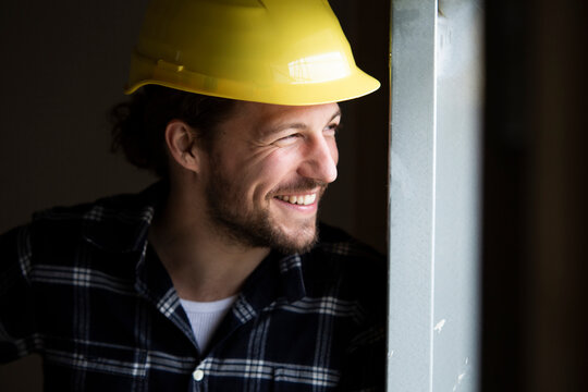 Close-up of smiling construction worker wearing helmet looking away by wall in house