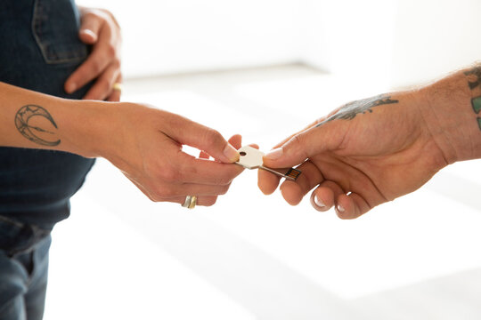 Close-up of couple hands holding USB key in new house