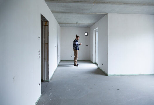 Construction worker standing in empty house at construction site