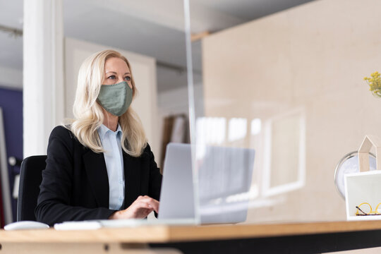 Businesswoman wearing mask using laptop on desk at home during curfew