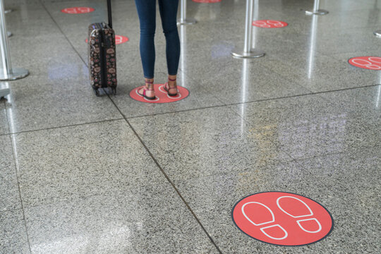 Legs of woman standing on markings for social distancing at airport
