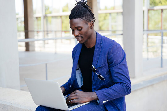 Young man using laptop while sitting on retaining wall