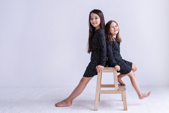 Smiling daughters sitting on table against white background in studio
