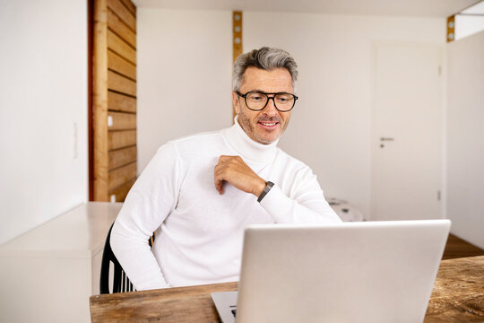 Smiling mature male entrepreneur using laptop on desk in office