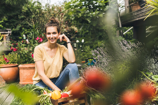 Beautiful woman with vegetables sitting amidst plants in community garden