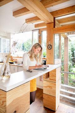 Female entrepreneur using digital tablet on desk while standing in office