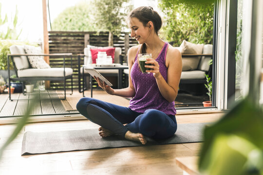Smiling young woman holding drink while using digital tablet on exercise mat at home