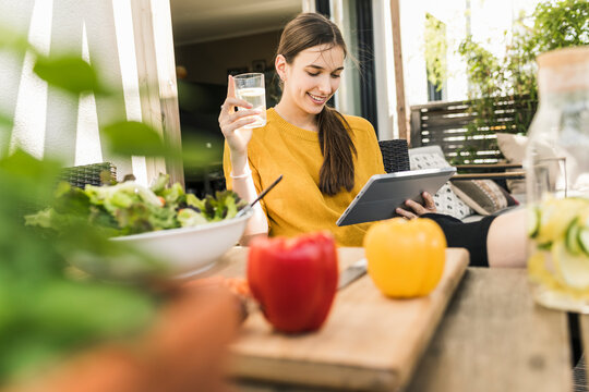 Smiling young woman with vegetables on table watching video over digital tablet at home