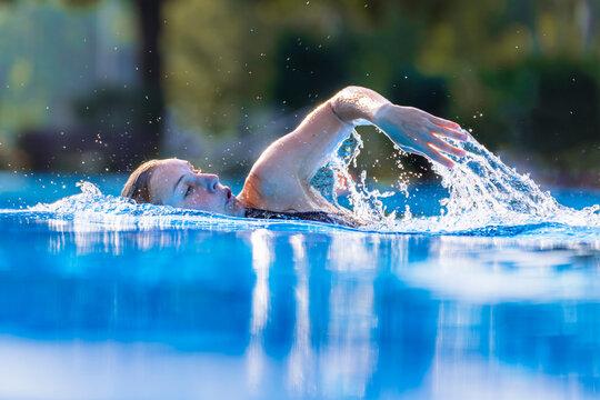 Beautiful woman swimming in swimming pool