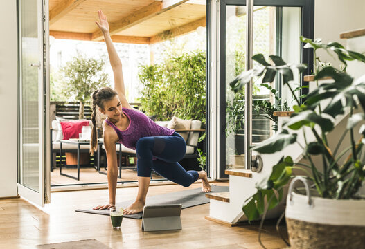 Young woman exercising while looking in digital tablet at home