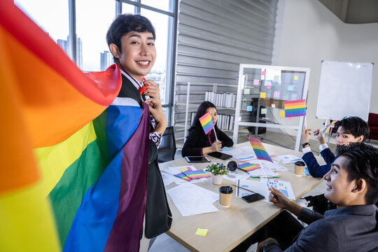 Homosexual Asian businessman with LGBT flag and Successful happy workers with in company  workers Group of asian business people and support in the meeting room at office