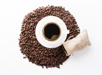 Plano cenital de una taza de café caliente americano con granos tostados de café sobre la mesa color blanco con un saco pequeño