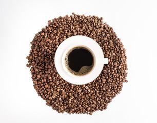 Plano cenital de una taza de café caliente americano con granos tostados de café sobre la mesa color blanco
