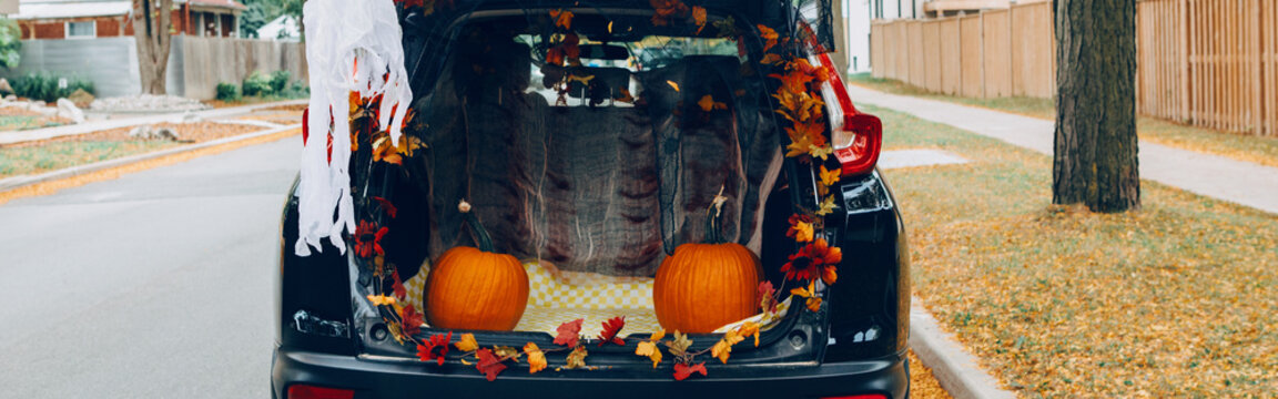 Trick or trunk. Black car trunk decorated for Halloween. Autumn fall decor with red pumpkins and yellow leaves for traditional October holiday outdoors. Web banner header.