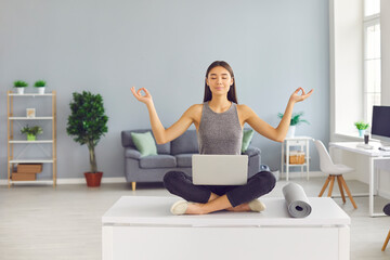 Young woman sitting in lotus position on office table and practicing yoga and meditation