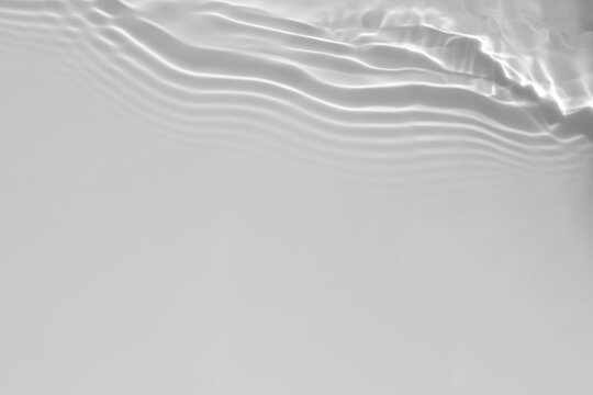 de-focused. Blurred desaturated transparent clear calm water surface texture with splashes and bubbles. Trendy abstract nature background. White-grey water waves in sunlight. Copy space.