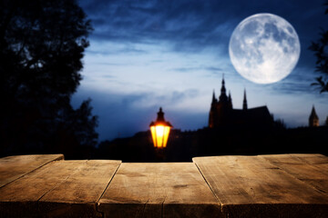Halloween Holiday concept. Empty rustic table in front of scary night sky, forest and full moon background. Ready for product display montage