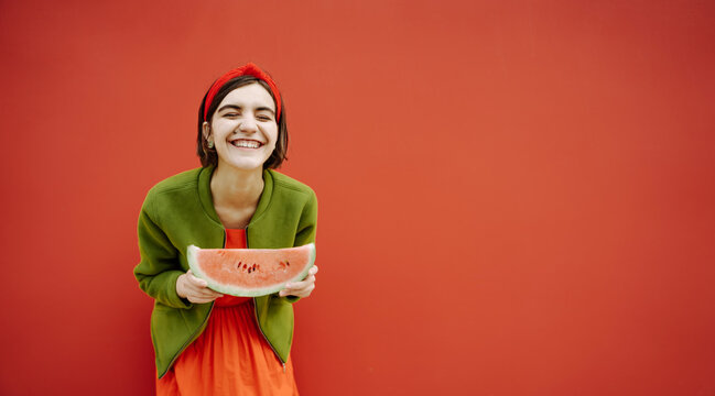 Adorable laughing brunet teen girl in green jacket and red dress. Hair accessories. Holding slice of watermelon. Funny joke. sense of humor concept. Looking to the camera teeth smile. Street style