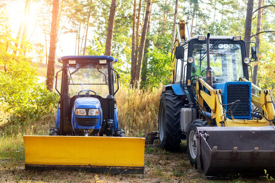 Two small and big modern tractors parked at backyard near forest farm at countryside. Residential home technic and agricultural equipment. Machinery parked for maintenance and storage outdoors