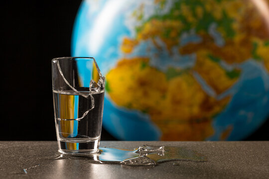 broken glass and its fragments with leaking water on the background of the globe, map of the African continent