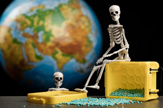 the skeleton sits on a yellow box from which beads are pouring out, the background is the planet earth