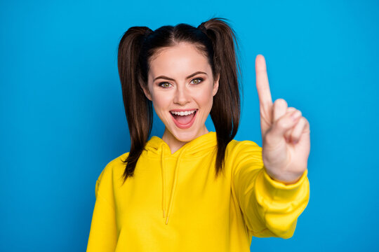 Ready steady go. Photo of pretty lady two tails raise arm showing one index fingers good mood counting set start wear casual yellow hoodie pullover isolated bright blue color background