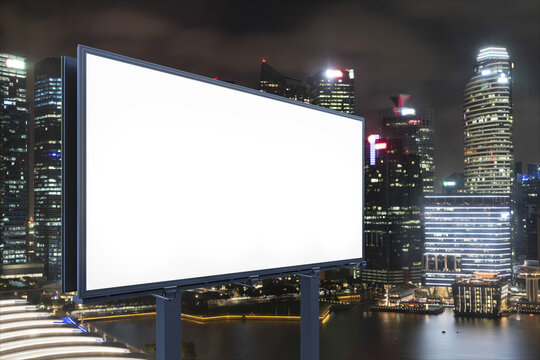 Blank white road billboard with Singapore cityscape background at night time. Street advertising poster, mock up, 3D rendering. Side view. The concept of marketing communication to sell idea.