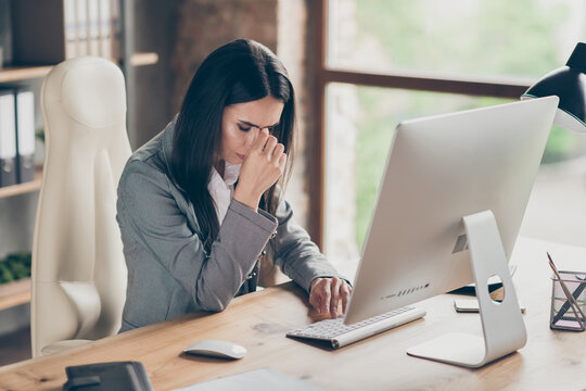 Photo of frustrated girl lawyer agent collar sit desk table get pc computer social network job loss covid quarantine crisis notification touch nose fingers wear blazer in modern office