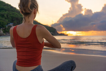 Woman practices yoga. Woman sitting in lotus position and meditating at sunrise on the beach