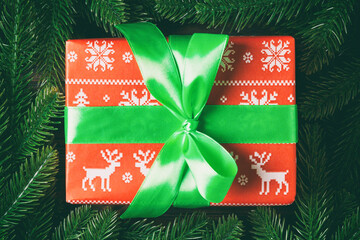 Wall Mural - Top view of Christmas gift box on fir tree background. Time for holiday concept with copy space