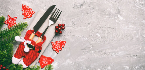Wall Mural - Top view Banner of festive cutlery on new year cement background. Christmas decorations with empty space for your design. Holiday dinner concept