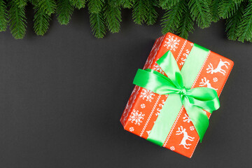 Wall Mural - Top view of fir tree branches and gift box on colorful background. Christmas time concept with empty space for your design