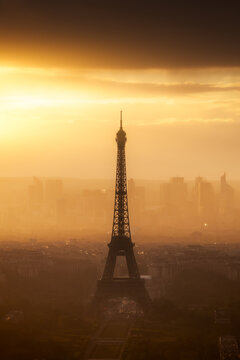 A misty sunset around the Eiffel Tower and the headquarter of La Défense