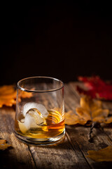 Glass of scotch whiskey and ice on wooden background with autumn leaves