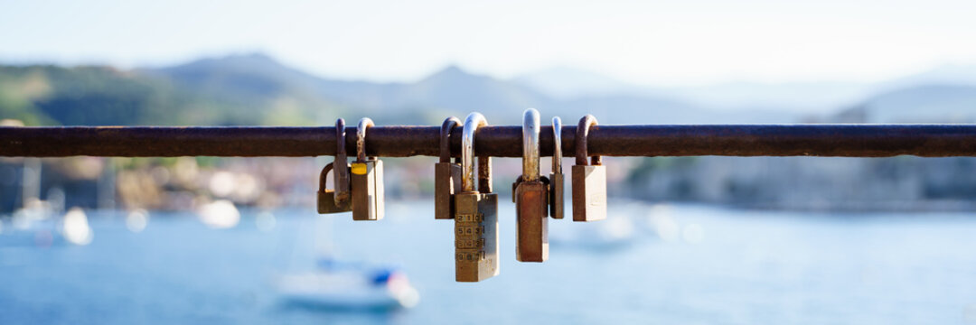 Panoramic view of rusty locks on a seafront railing