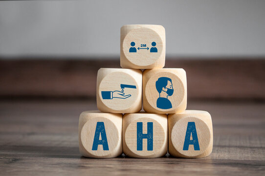 Cubes and dice with hygiene icons covid-19 corona virus and the german acronym for AHA - Abstand, Hygiene, Alltagsmaske on wooden background
