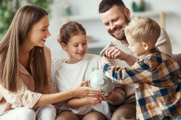 financial planning   family mother father and children with piggy Bank at home