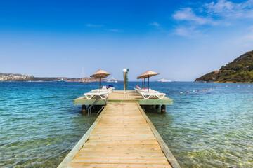 Beach wooden pier with sun umbrellas and beach loungers in Mediterranean sea