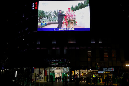 A giant screen shows news footage of Chinese President Xi Jinping presenting a flower basket to the statue of former Chinese leader Deng Xiaoping at a park in Shenzhen, outside a shopping mall in Beijing