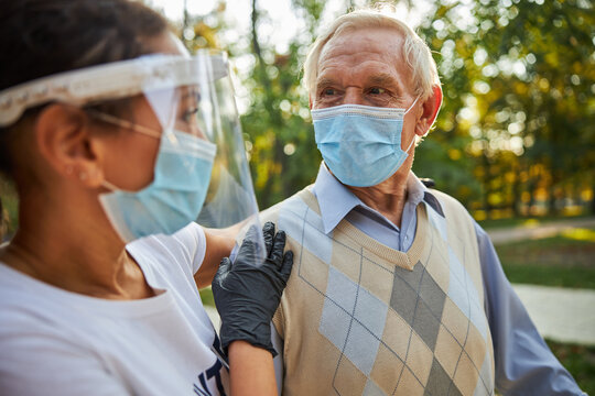 Senior man looking to the eyes of female in medicine mask