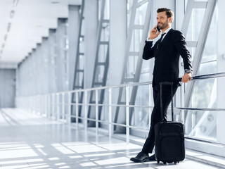 Happy wealthy businessman standing in airport, talking on mobile phone