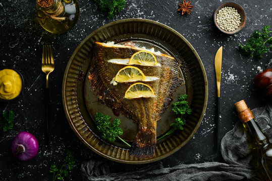 Baked flounder fish with lemon and spices on a metal baking dish. Seafood. Top view. Free space for text.
